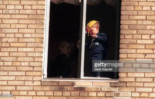 Actor Tony Randall's child gets dangerously close to an open window November 23 2000 while watching the Macy's Thanksgiving Day Parade in New York...