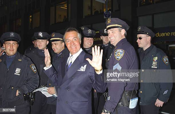 Actor Tony Sirico gestures as he stands near New York City police officers before entering Radio City Music Hall for the premiere of 'The Sopranos'...