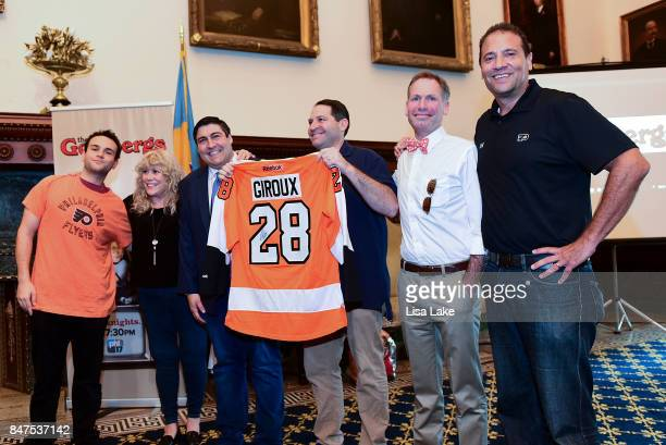 Actor Troy Gentile Beverly Goldberg guest and Ike Richman VP of Public relations at ComcastSpector presents Producer Adam F Goldberg with official...