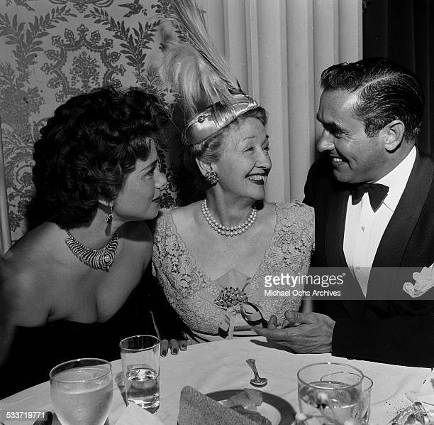 Actor Tyrone Power and his wife actress Linda Christian are greeted by Gossip Columnist Heddy Hopper during an event in Los AngelesCA