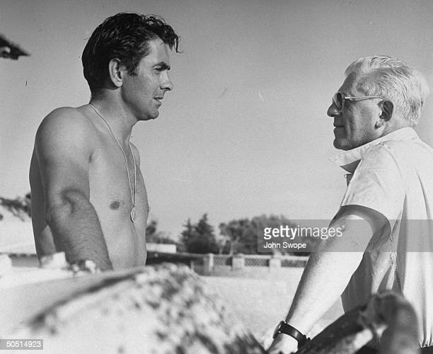 Actor Tyrone Power chatting with director Anatole Litvak while vacationing on French Riviera