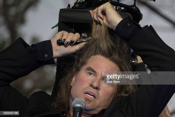 Actor Val Kilmer cuts his hair off on stage while filming the new Terrence Malick movie during day one of Fun Fun Fun Fest at Auditorium Shores on...