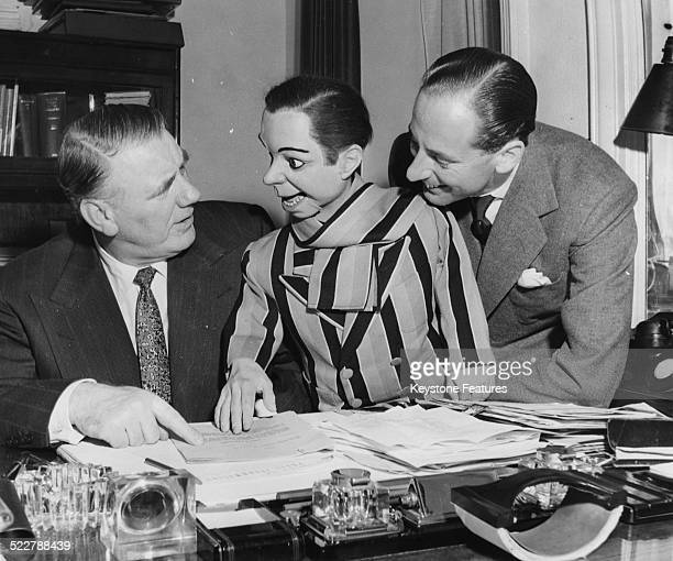 Actor Val Parnell and ventriloquist Peter Brough with his puppet Archie Andrews joking around at a writing desk circa 1965