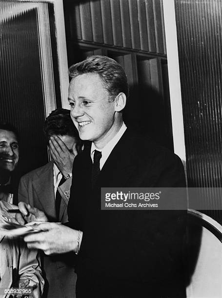 CA Actor Van Johnson stops to sign his autograph for fans in Los Angeles California