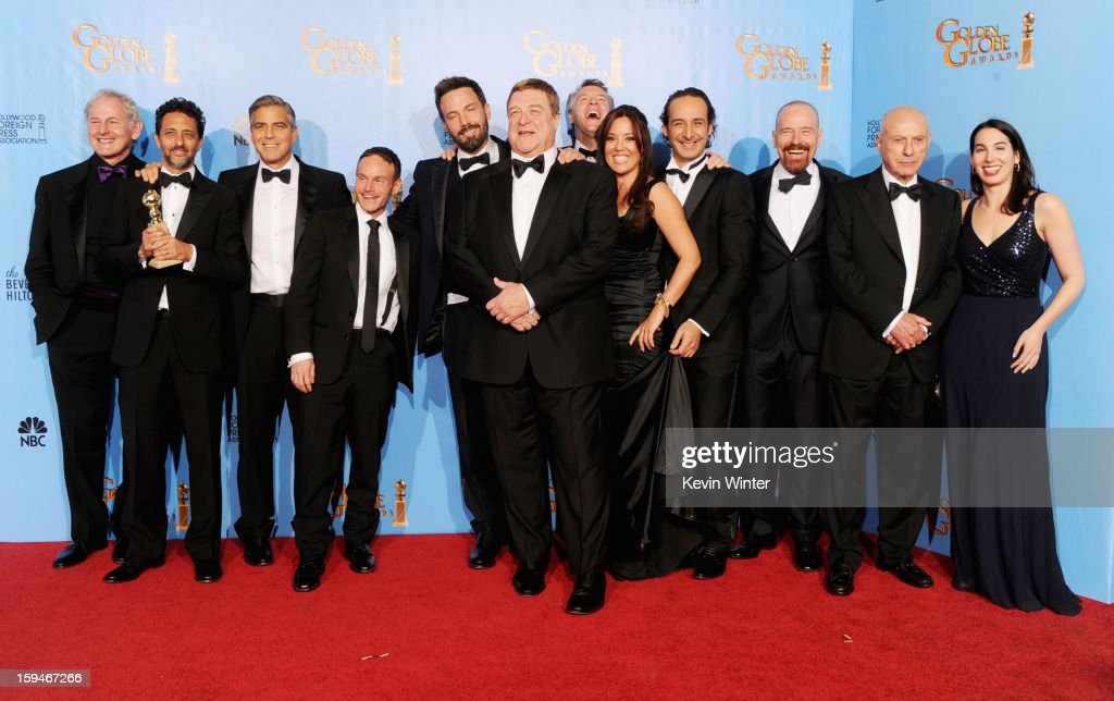 L-R) Actor Victor Garber, Producers Grant Heslov and Gorge Clooney, writer Chris Terrio, Director Ben Affleck, actors John Goodman, Tate Donovan, producer Chay Carter, composer Alexandre Desplat, actors Bryan Cranston, Alan Arkin and guest of 'Argo', winner Best Motion Picture, Drama, pose in the press room during the 70th Annual Golden Globe Awards held at The Beverly Hilton Hotel on January 13, 2013 in Beverly Hills, California.