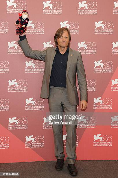 """Actor Viggo Mortensen holds a 'Freud' doll as he attends the """"A Dangerous Method"""" photocall during the 68th Venice International Film Festival at..."""