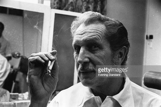 Actor Vincent Price enjoying a cigarette in his dressing room