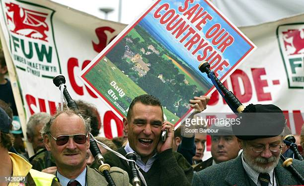 Actor Vinnie Jones laughs while speaking on a cellular telephone as he marches with people through central London to highlight the needs of rural...