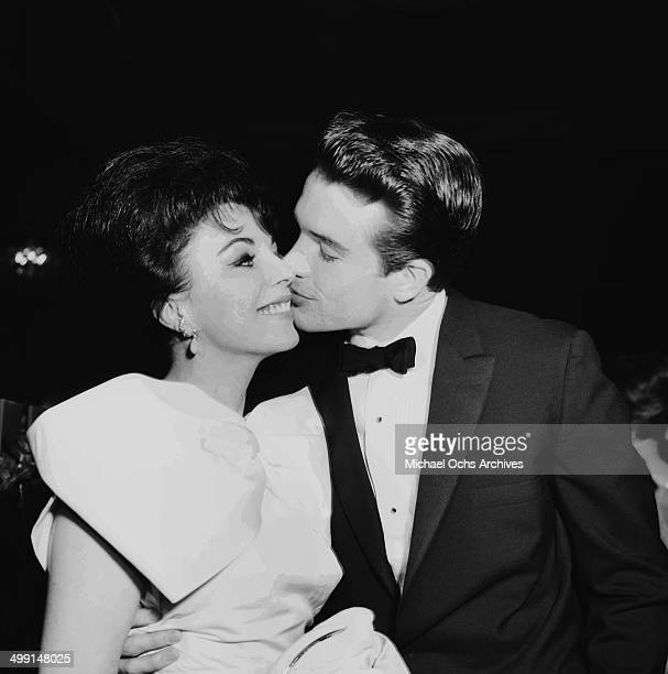 Actor Warren Beatty kisses actress Joan Collins as they attend a party in Los Angeles California