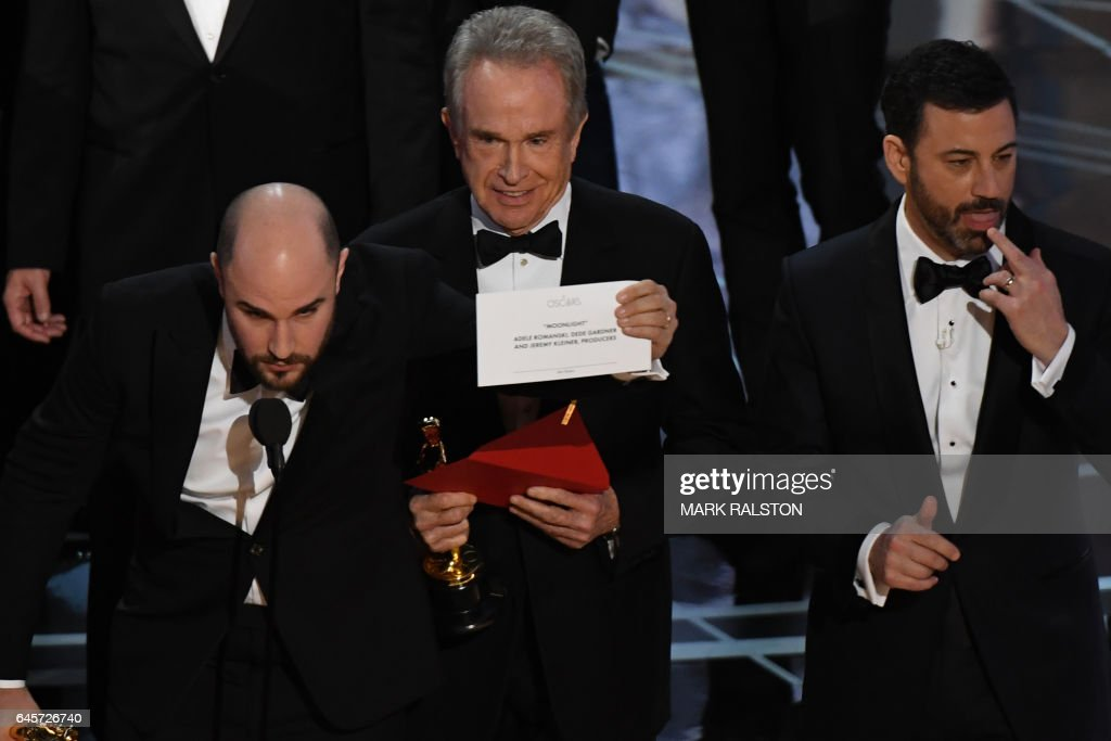 US actor Warren Beatty (C) shows the card reading Best Film 'Moonlight' next to 'La La Land' producer Jordan Horowitz (L) and host Jimmy Kimmel after mistakingly reading 'La La Land' initially at the 89th Oscars on February 26, 2017 in Hollywood, California. / AFP / Mark RALSTON