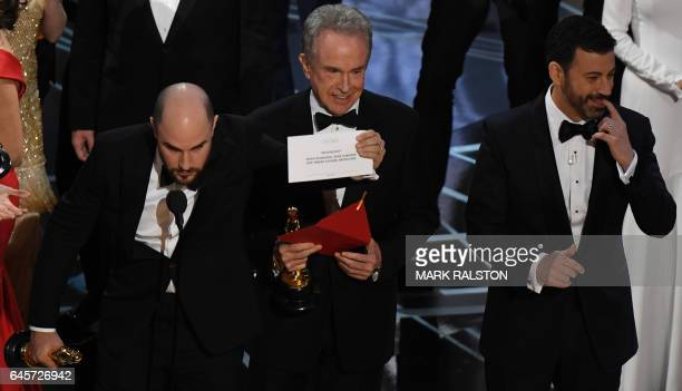 US actor Warren Beatty shows the card reading Best Film 'Moonlight' next to 'La La Land' producer Jordan Horowitz and host Jimmy Kimmel after...