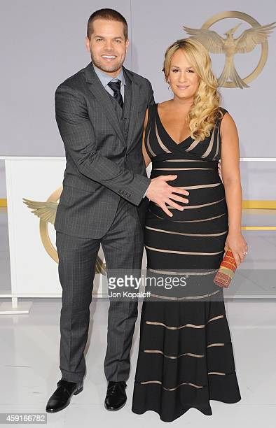 Actor Wes Chatham and Jenn Brown arrive at the Los Angele Premiere The Hunger Games Mockingjay Part 1 at Nokia Theatre LA Live on November 17 2014 in...