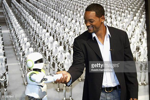 Actor Will Smith poses with humanoid robot PINO at a press conference to promote the film 'I Robot' September 7 2004 in Tokyo Japan