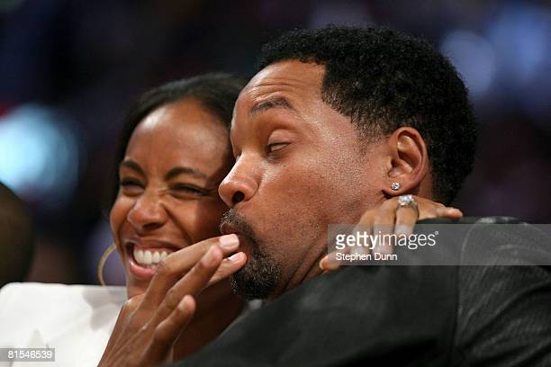 Actor Will Smith reacts after his wife, actress Jada Pinkett Smith, kisses him at the start of the fourth quarter of Game Four of the 2008 NBA Finals...