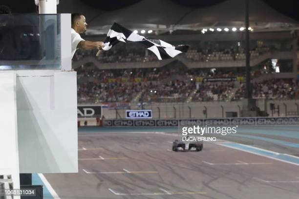 TOPSHOT US actor Will Smith waves the checkered flag as Mercedes' British driver Lewis Hamilton crosses the finish line during the Abu Dhabi Formula...