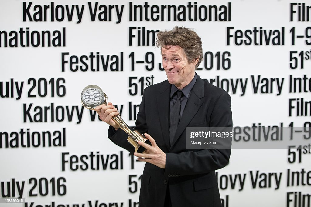 Actor Willem Dafoe poses for photographers with the Crystal Globe Award for Outstanding Artistic Contribution to World Cinema at the opening ceremony of the 51st Karlovy Vary International Film Festival (KVIFF) on July 1, 2016 in Karlovy Vary, Czech Republic.
