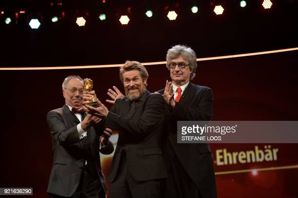 TOPSHOT US actor Willem Dafoe receives from Berlinale Director Dieter Kosslick the Honorary Golden Bear award as US director Wim Wenders applauds...