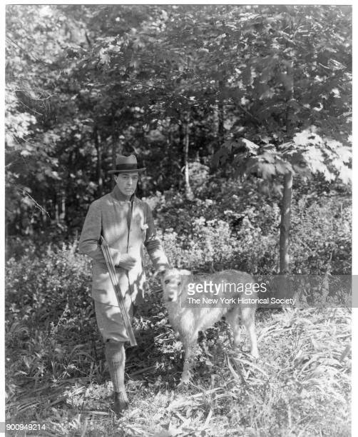 Actor William Faversham in breeches coat and hat holding a rifle stands in a wood with a dog 1922