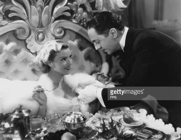 Actor William Powell pictured serving actress Carole Lombard breakfast in bed in a scene from the film 'My Man Godfrey' USA 1936