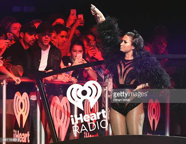 Actor Wilmer Valderrama and recording artist/actor Nick Jonas look on as singer/songwriter and actress Demi Lovato performs at the 2015 iHeartRadio...
