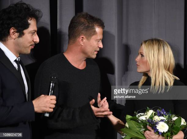 Actor Yalcin Gumer actor Til Schwieger and singer Helene Fischer stand on stage at the premiere of the film 'Der grosse Schmerz' from the TV series...