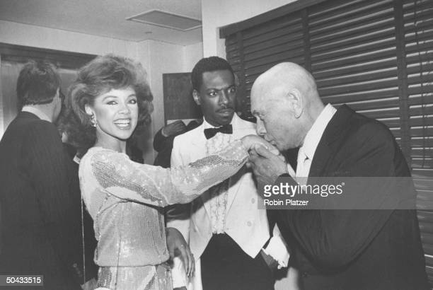 Actor Yul Brynner coowner of the Hard Rock Cafe kissing the hand of Miss America Vanessa L Williams as comedian Eddie Murphy looks on at the cafe's...
