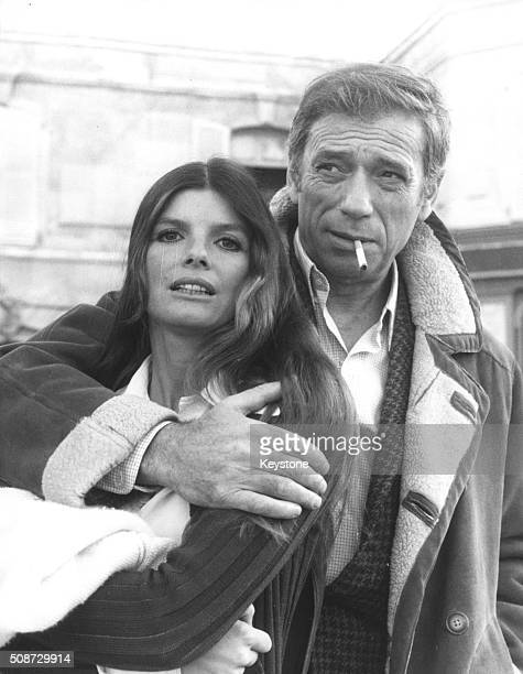 Actor Yves Montand smoking a cigarette with his arm around actress Katharine Ross during a break in filming scenes for 'Le Hasard et la Violence'...