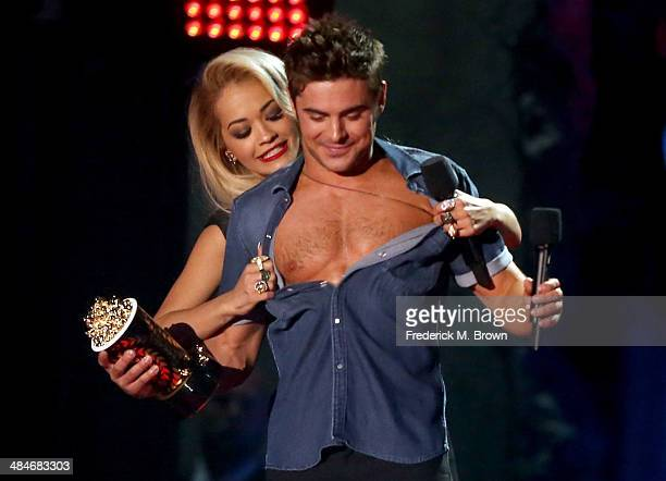 Actor Zac Efron accepts the Best Shirtless Performance award for 'That Awkward Moment' from singer Rita Ora onstage at the 2014 MTV Movie Awards at...