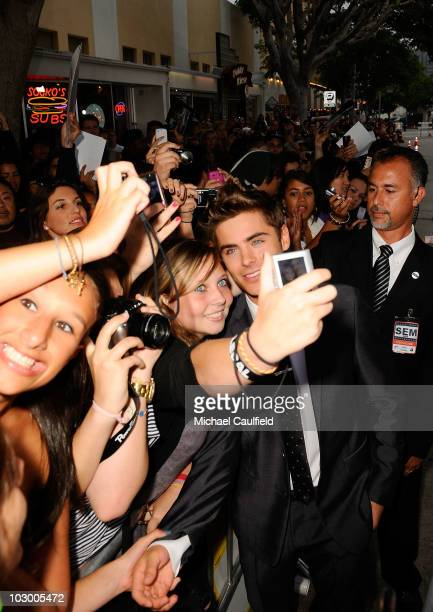 Actor Zac Efron poses for pictures with fans as he arrives at the premiere of Universal Pictures' Charlie St Cloud held at the Regency Village...
