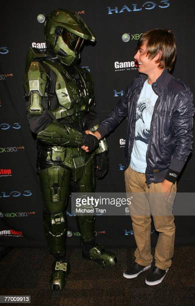 Actor Zac Efron poses with character Master Chief from Halo 3 at Gamestop a videogame store on September 24 2007 at Universal Citywalk in North...