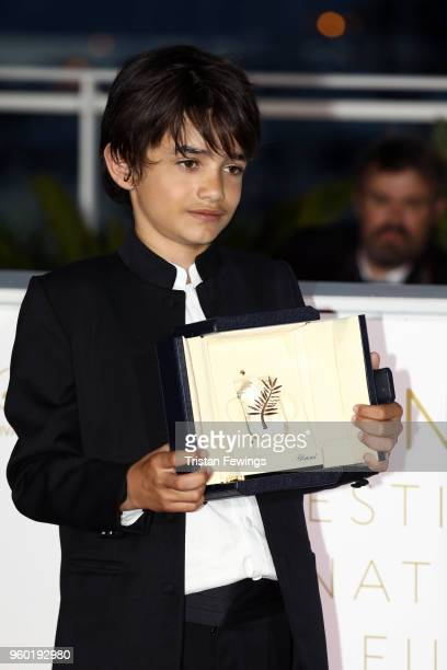 Actor Zain Alrafeea poses with Director Nadine Labaki's Jury Prize award for 'Capharnaum' at the Palme D'Or Winner Photocall during the 71st annual...