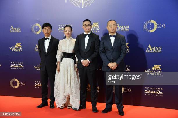 Actor Zhang Yu actress Tan Zhuo and director Wen Muye pose on the red carpet of the 13th Asian Film Awards on March 17 2019 in Hong Kong China