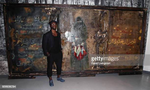 Actor/artist Aldis Hodge poses with his art at Art with a Cause hosted by Shaun Ross Aureta benefiting the Freedom United Foundation for the victims...