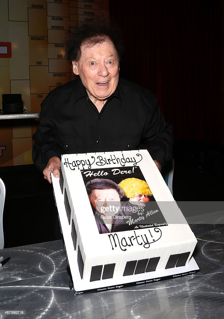 Actor/comedian Marty Allen holds up a cake to celebrate his 93rd birthday during a meet and greet after his performance at the Downtown Grand Hotel & Casino on March 23, 2015 in Las Vegas, Nevada.