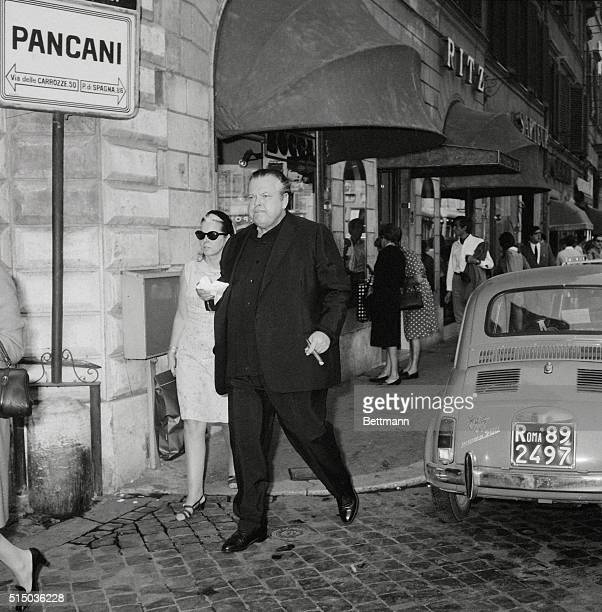 Actordirector Orson Welles and his secretary Miss M Coppiello go for a stroll on Rome's fashionable Via Condotti He is appearing in House of Cards...