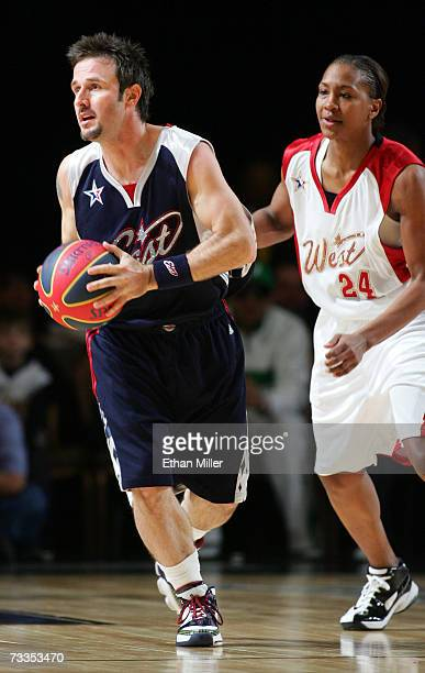 Actor/east coast player David Arquette drives the ball as NBA Indiana Fever's/west coast player Tamika Catchings follows during the McDonald's NBA...