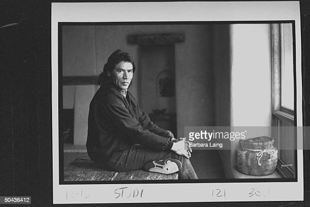 Actor/Indian activist Wes Studi sitting atop an old weatherbeaten table at home