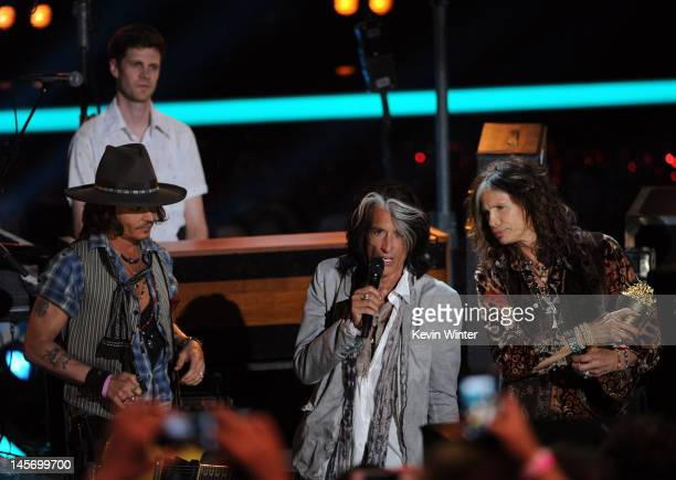Actor/musician Johnny Depp accepts the MTV Generation Award from musicians Steven Tyler and Joe Perry onstage during the 2012 MTV Movie Awards held...