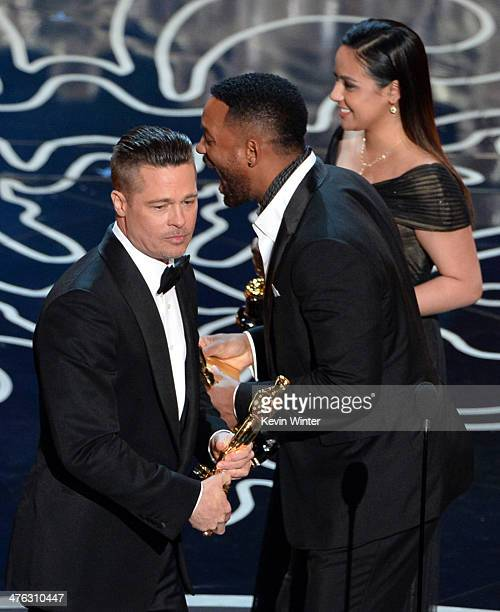Actor/producer Brad Pitt accepts the Best Picture award for '12 Years a Slave' from actor Will Smith onstage during the Oscars at the Dolby Theatre...