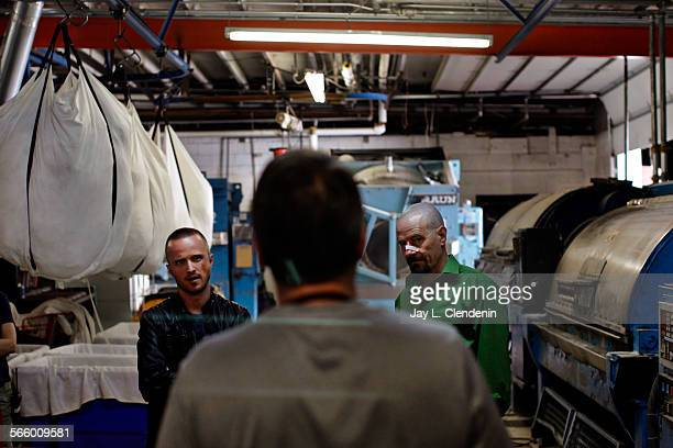 Actors Aaron Paul left and Bryan Cranston right listen to direction from show creator and episode director Vince Gilligan on location at an...