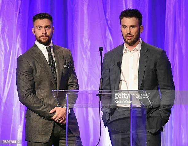 Actors Aaron Taylor-Johnson and Chris Evans speak onstage at the Hollywood Foreign Press Association's Grants Banquet at the Beverly Wilshire Four...