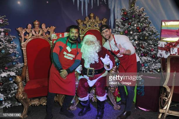 Actors Adrian Dev and Luke Guidan pose with Santa Claus at the Los Angeles Mission Christmas On Skid Row held at Los Angeles Mission on December 21...
