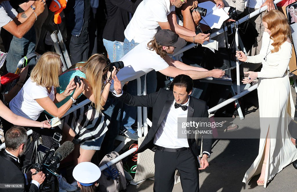 US actors Adrien Brody (C) and Jessica Chastain (R) sign autographs on May 21, 2013 as they arrive for the screening of the film 'Cleopatra' presented in Cannes Classics at the 66th edition of the Cannes Film Festival in Cannes. Cannes, one of the world's top film festivals, opened on May 15 and will climax on May 26 with awards selected by a jury headed this year by Hollywood legend Steven Spielberg.