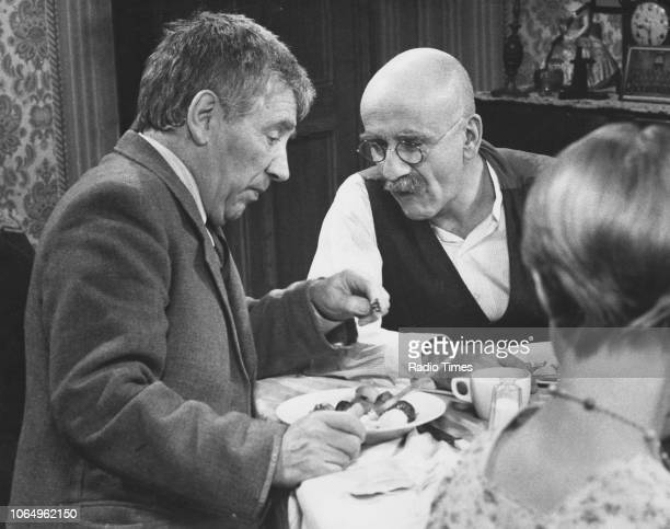 Actors Alfie Bass and Warren Mitchell smoking in a dinner table scene from the television sitcom 'Till Death Us Do Part' December 15th 1974