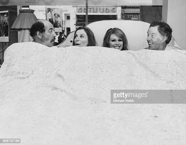 Actors Alfred Marks Deborah Grant Joanna Lumley and Brian Rix lying in bed together in the window of Maples department store promoting their West End...
