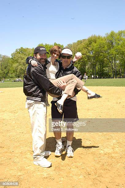Actors Alfred Molina and Alec Balwin give actress Susan Egan a lift at the opening day of the Broadway Softball League in New York City on May 6 2004...