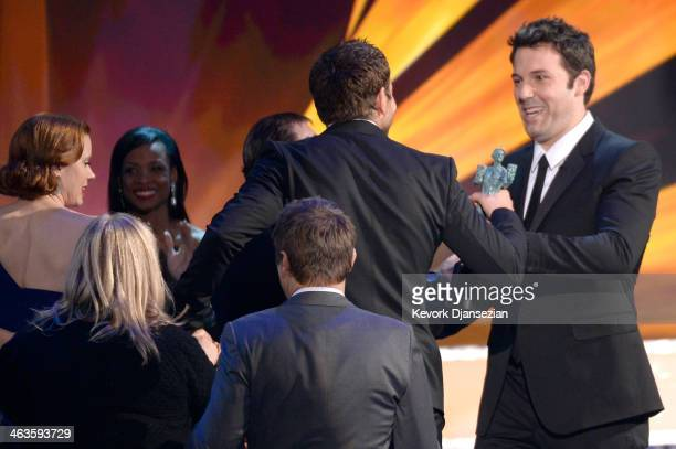 Actors Amy Adams and Bradley Cooper accept the Outstanding Performance by a Cast in a Motion Picture award for 'American Hustle' from actor Ben...