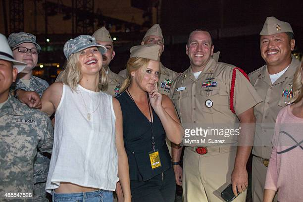 Actors Amy Schumer and Jennifer Lawrence pose with servicemen and women backstage at the sold out Billy Joel concert at Wrigley Field on August 27...