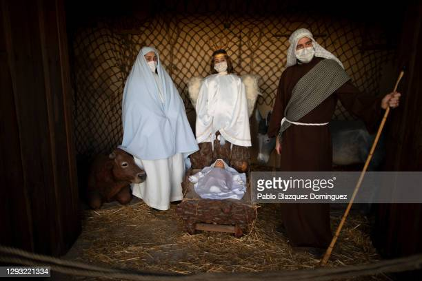 Actors and actress Montse, her son Mateo and her husband Javier wear face masks while they perform as the Virgin Mary, an angel and Saint Joseph...