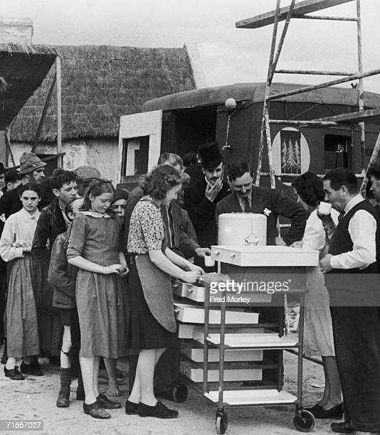 Actors and extras from Frank Launder's film 'Captain Boycott' break for a cup of tea during production at Pinewood Studios Iver Buckinghamshire 21st...